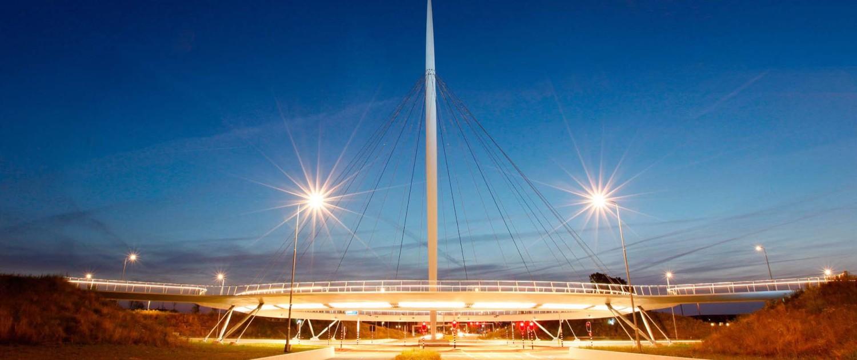 zwevende fietsrotonde Hovenring Eindhoven kruising Heerbaan slank cirkelvormig dek en krachtig vormgegeven stalen pyloon