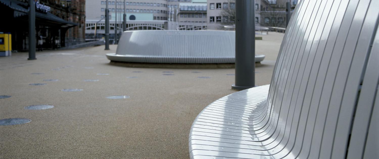 cirkelvormige banken stadsbalkon Groningen stationsplein zilverkleurige gebogen stalen strips overdag, meubilairontwerp door ipv Delft