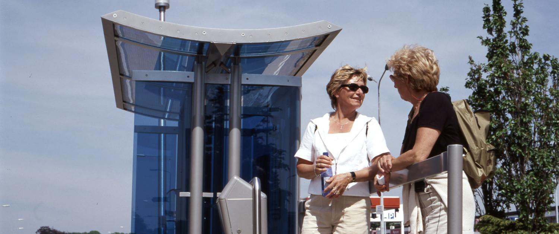 abri ontwerp buitenstijl Regionaal Vervoer Limburg aluminiumkleurig staal en lichtgebogen lijnen blauw glas