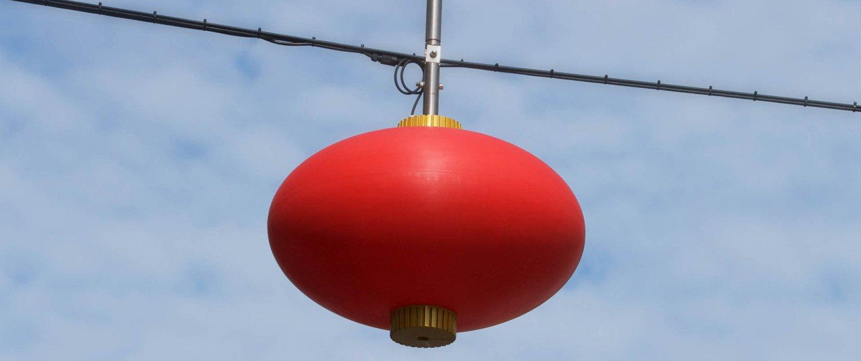 lampionnen Chinatown Den Haag verlichting Wagenstraat close-up lichtontwerp helderrode kunststof bol en goudkleurig aluminium boven- en onderzijde