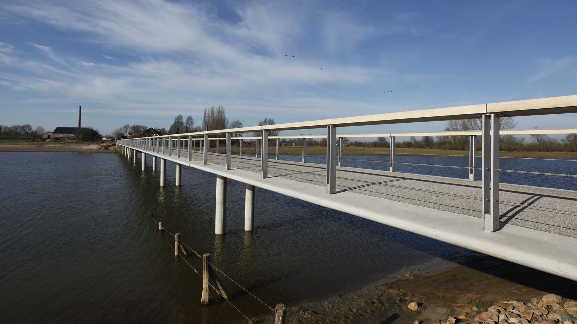 zijaanzicht brugontwerp met betonnen steunpilaren, hydrodynamisch, duurzaam en overstroombaar ontwerp van ipv Delft in Fortmond Olst