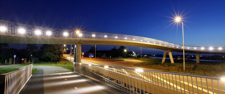 fietsbrug over N242, betonnen pilaren en transparant hekwerk, fietsbrug 's avonds, Stationsweg Heerhugowaard, brugontwerp door ipv Delft