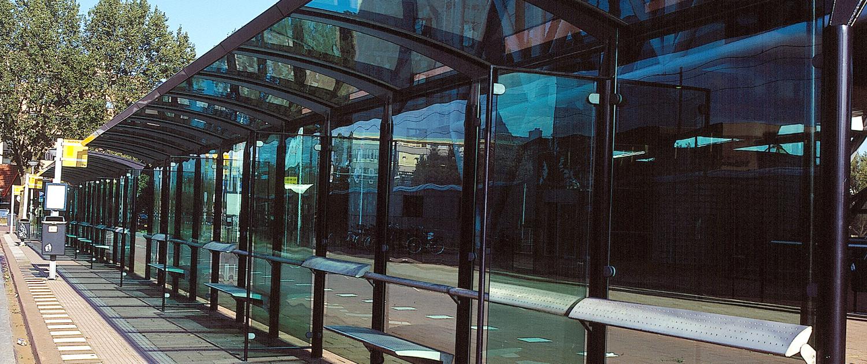 abri's buitenstijl Stationsplein Rijswijk Generaal Eisenhowerplein zakelijke uitstraling abri duidelijke vormtaal glazen wanden en gebogen dakvorm voor schuilfunctie