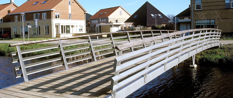 fietsbrug Burmaniapark Smallingerland Drachten bruggenfamilie strak ontwerp staal, hout en driehoeken U-profielen randliggers stalen hekwerk met houten handregel