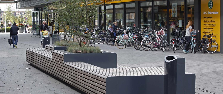 ontwerp straatmeubilair houten XXL-bank met strakke ijzeren zijpanelen en met verschillende zitniveaus en vrijstaande boombakken, stadscentrum Zwolle