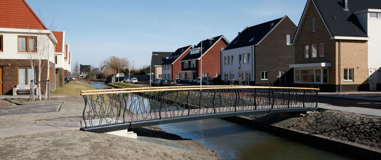 zijaanzicht brug van staal met betonnen wegdek en gebogen staalstrips, bloemen verwerkt in het hekwerk, Tuinveld 'S Gravenzande, brugontwerp door ipv Delft