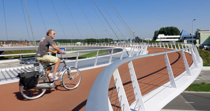 fietser op hovenring eindhoven, moderne pyloonbrug over de snelweg, fietsbrug ontwerp door ipv Delft