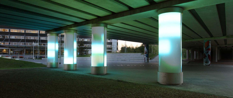 lichtzuilen op Schiphol in groentinten, lichtarchitectuur in onderdoorgang