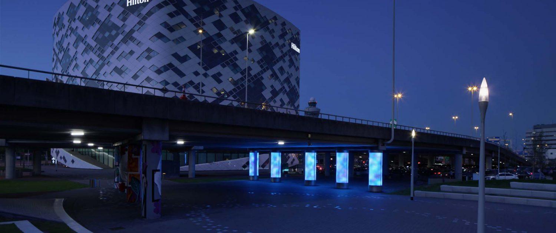 lichtzuilen in blauwtinten onder autoweg bij schiphol, verlichtingsarchitectuur